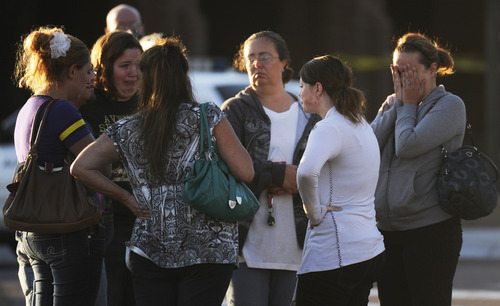 A group of friends are overcome with emotion as they gather outside Gateway High School, Friday July 20, 2012, in Aurora, Colo. They recieved news that their friend was killed during a shooting early Friday inside the Aurora movie theater.  A gunman wearing a gas mask set off an unknown gas and fired into the crowded movie theater killing 12 people and injuring at least 50 others, authorities said. (AP Photo/The Denver Post,  RJ Sangosti)