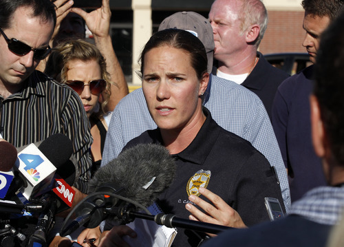 Sgt. Cassidy Carlson, center, spokesperson for the Aurora Police Department, speaks during a media availability near the apartment of alleged gunman James Holmes, Saturday, July 21, 2012, in Aurora, Colo. Authorities reported that 12 people died and dozens more were shot during an assault at a movie theater midnight premiere of