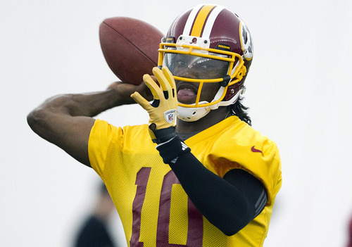 FILE - This May 21, 2012 file photo shows Washington Redskins rookie quarterback Robert Griffin III throwing a pass during practice in Ashburn, Va. Griffin has agreed to terms on a contract with the Redskins. Griffin's agent, Ben Dogra, told The Associated Press that the Heisman Trophy-winning quarterback agreed to terms and will be in Redskins rookie camp on Wednesday, July 18, 2012. (AP Photo/Evan Vucci, File)