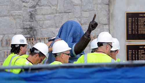 Penn State Office of Physical Plant workers cover the statue of former football coach Joe Paterno near Beaver Stadium on Penn State's campus in State College, Pa., on Sunday, July 22, 2012. The university announced earlier Sunday that it was taking down the monument in the wake of an investigative report that found the late coach and three other top Penn State administrators concealed sex abuse claims against retired assistant coach Jerry Sandusky. (AP Photo/Centre Daily Times, Christopher Weddle)