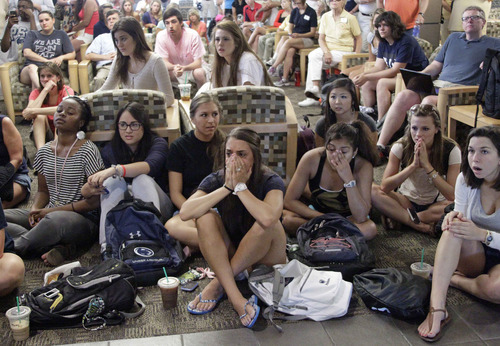 Penn State students and employees reacts as they listen to a television in the HUB on the Penn State University main campus in State College, Pa., as the NCAA sanctions against the Penn State University football program are announced Monday, July 23, 2012.  (AP Photo/Gene J. Puskar)