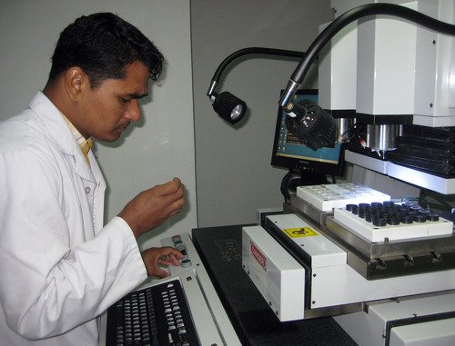 Tony Semerad  |  The Salt Lake Tribune  Technician Dharmendra Chaudhary examines a hard intraocular lens implant being manufactured at Tilganga Eye Clinic in Kathmandu, Nepal. The facility produces about 30,000 lenses monthly, with each 18-millimeter diameter circle of glass machined to exacting international standards. Lens are exported to Pakistan, China, Turkey and elsewhere to subsidize patient care. The clinic has restored vision to hundreds of thousands of blind Nepali and brought high-quality, inexpensive eye surgeries to one of the world's poorest regions-- with pivotal help and inspiration from a top ophthamologist at the John A. Moran Eye Center in Salt Lake City.