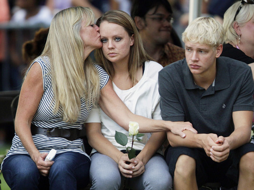 Family members of the victims of Friday's mass shooting in Aurora, Colo., comfort each other, Sunday, July 22, 2012, in Aurora, Colo., during a prayer vigil for the victims. Twelve people were killed and dozens were injured in a shooting attack Friday at the packed theater during a showing of the Batman movie,