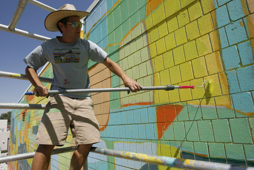 Francisco Kjolseth  |  The Salt Lake Tribune Community artist Chris Peterson comes up on 14-days of painting for his mural on the Sorenson Unity Center's backyard art park. The 105 foot long and 30 feet tall mural depicts the Glendale neighborhood and surounding areas along the Jordan River.