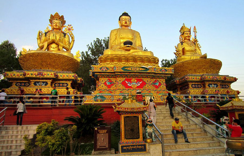 Statues of Chenrezig, the Shakyamuni Buddha and Guru Rinpoche, at Swayambhunath Stupa in Kathmandu, Nepal. The ancient mountain complex of shrines, monuments, statuary and long sequences of prayer wheels is considered one of the most sacred Buddhist sites in the Kathmandu valley. Courtesy Jared Kee