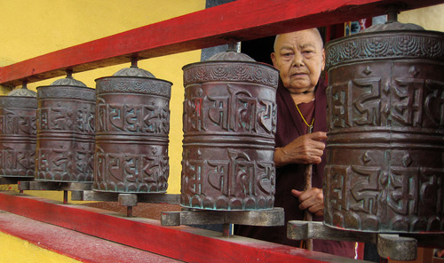 Tony Semerad  |  The Salt Lake Tribune  A nun looks out from behind a row of prayer wheels at Nagi Gompa, Nepal, outside the capital Kathmandu. Nagi Gompa is a verdant, peaceful mountainside hermitage that is closely linked with Tibetan Buddhist master Tulku Urgyen Rinpoche, who died in 1996. A group of Utah Buddhists toured of Nagi Gompa in June as part of a religious pilgrimage to Nepal, a trip intended to strengthen their ties with teachers and sites considered sacred in Vajrayana Buddhism.