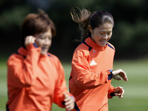 Japan's Homare Sawa, left, looks at her watch as she runs during a training session at the London 2012 Summer Olympics, in Coventry, England Thursday, July 26, 2012. (AP Photo/Hussein Malla)