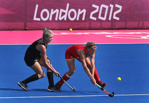 Belgium's Helene Delmee, right, vie the ball as New Zealand's Samantha Harrison challenges during their practice field hockey match in Riverbank Arena at the 2012 Summer Olympics, Thursday, July 26, 2012, in London. (AP Photo/Eranga Jayawardena)