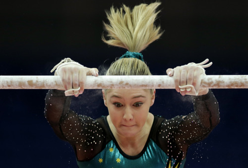 An Australian gymnast performs on the uneven bars during training at the 2012 Summer Olympics, Thursday, July 26, 2012, in London. (AP Photo/Gregory Bull)