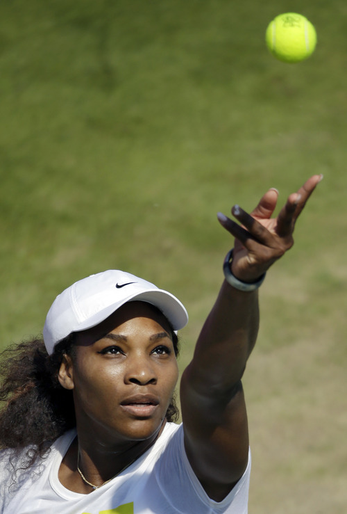 Serena Williams of the United States serves as she practices at the All England Lawn Tennis Club at Wimbledon, London for the 2012 Summer Olympics, Thursday, July 26, 2012. Tennis competition is scheduled to begin Saturday, July 28. (AP Photo/Elise Amendola)