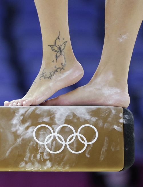 Italy's Vanessa Ferrari strikes a pose as she performs on the beam during training at the 2012 Summer Olympics, Thursday, July 26, 2012, in London. (AP Photo/Julie Jacobson)