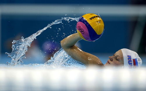 Water splashes as Russia women's water polo player Evgeniia Khokhriakova swims with the ball during a training session prior to the start of the 2012 Summer Olympics, Thursday, July 26, 2012, in London. The opening ceremonies for the 2012 London Olympics will be held Friday, July 27. (AP Photo/Julio Cortez)
