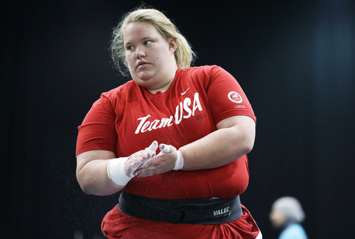 Holley Mangold, of the United States, chalks her hands in the weightlifting training area at the 2012 Summer Olympics, Thursday, July 26, 2012, in London. (AP Photo/Hassan Ammar)