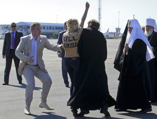 This photo made available by Femen shows a topless protester from the controversial Ukrainian feminist group Femen, center, is blocked by a security guard, left, and a priest, right, as she tries to throw herself at the leader of the Russian Orthodox Church, Patriarch Kirill in Kiev, Ukraine Thursday, July 26, 2012. The woman, identified as Anna Zhdanova, had the words