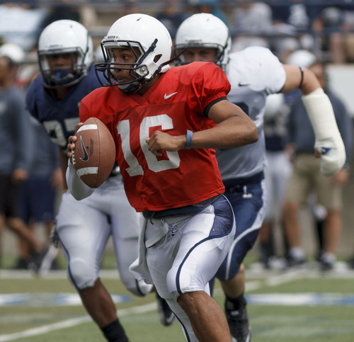 Trent Nelson  |  The Salt Lake Tribune Quarterback Chuckie Keeton scrambles at Utah State's annual Blue and White football game Saturday, April 28, 2012 in Logan, Utah.