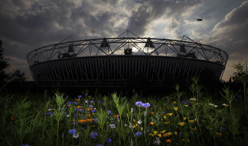 In this Wednesday, July 25, 2012 photo, a blimp flies in the sky as the sun sets behind the Olympic Stadium at the 2012 Summer Olympics, in London. A world city that needs no introduction, but scarred by terror bombings, riots and economic crisis since picked as Olympic host seven years ago, will launch the 2012 summer games with a spectacular opening ceremony Friday faced with a unique challenge: to be as memorable as Beijing's planet-wowing, money-no-object Olympic extravaganza of 2008. (AP Photo/Ben Curtis)