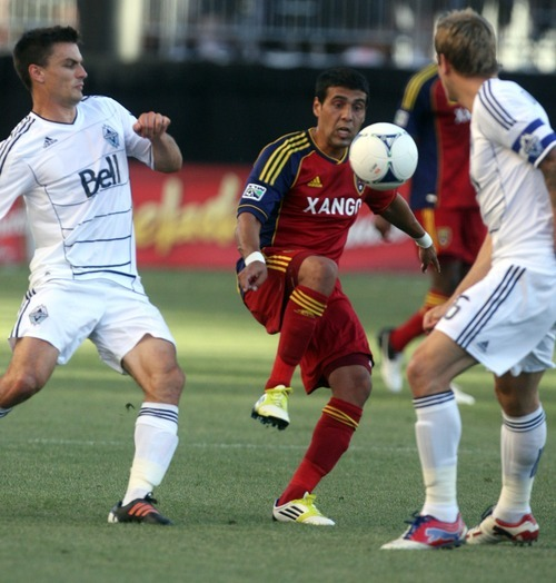 Kim Raff | The Salt Lake Tribune Real Salt Lake player Javier Morales maintains control of the ball against Vancouver player (left) Alain Rochat at Rio Tinto Stadium in Sandy, Utah on July 27, 2012.