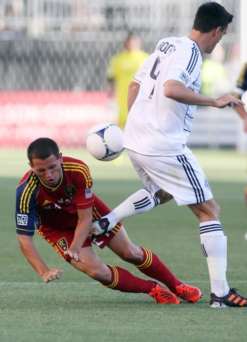 Kim Raff | The Salt Lake Tribune (left) Real Salt Lake player Luis Gil is kicked by Vancouver player Alain Rochat at Rio Tinto Stadium in Sandy, Utah on July 27, 2012.