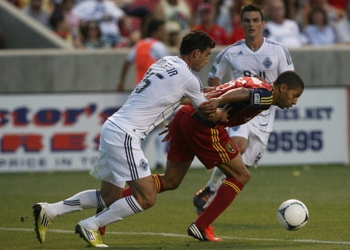 Kim Raff | The Salt Lake Tribune Real Salt Lake player Fabian Espindola shields the ball from Vancouver player Martin Bonjour at Rio Tinto Stadium in Sandy, Utah on July 27, 2012. Real Salt Lake went on to win the game 2-1.
