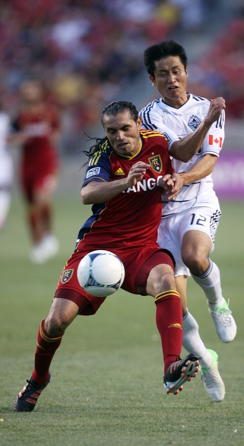 Kim Raff | The Salt Lake Tribune Real Salt Lake player Fabian Espindola collides with Vancouver player Lee Young-Pyo at Rio Tinto Stadium in Sandy, Utah on July 27, 2012. Real Salt Lake went on to win the game 2-1.