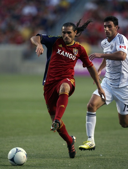 Kim Raff | The Salt Lake Tribune Real Salt Lake player Fabian Espindola dribbles the ball past  Vancouver player Martin Bonjour at Rio Tinto Stadium in Sandy, Utah on July 27, 2012. Real Salt Lake went on to win the game 2-1.