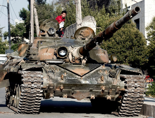 A Syrian boy sits atop a damaged military tank at the border town of Azaz, some 20 miles (32 kilometers) north of Aleppo, Syria. Turkey sealed its border with Syria to trucks on Wednesday, July 25, 2012 cutting off a vital supply line to the embattled nation as fighting stretched into its fifth day in the commercial capital of Aleppo. (AP Photo/Turkpix)