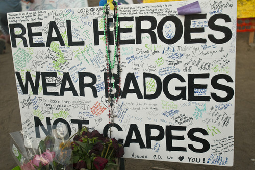 Chris Detrick     The Salt Lake Tribune A sign with handwritten messages to the victims at a memorial at South Sable Blvd and East Centrepoint Drive in Aurora Thursday July 26, 2012. The site is covered with hundreds of balloons, candles, flowers, stuffed animals, rosaries and many other items people have left behind in remembrance of the victims.
