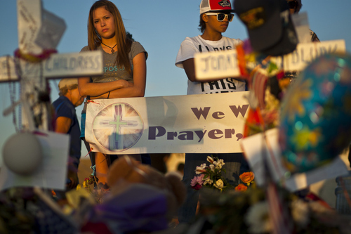 Chris Detrick     The Salt Lake Tribune Family, friends and community members reflect at a memorial set up for the shooting victims at South Sable Blvd and East Centrepoint Drive in Aurora Thursday July 26, 2012. The site is covered with hundreds of balloons, candles, flowers, stuffed animals, rosaries and many other items people have left behind in remembrance of the victims.