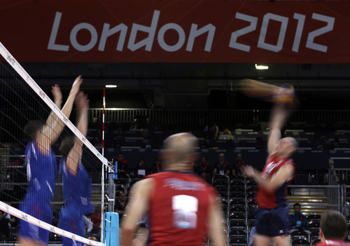 United States' Clayton Stanley, right, spikes the ball past two defenders from Serbia, at left, as Stanley's teammate, William Priddy, looks on during a men's preliminary volleyball match at the 2012 Summer Olympics, Sunday, July 29, 2012, in London. (AP Photo/Jeff Roberson)