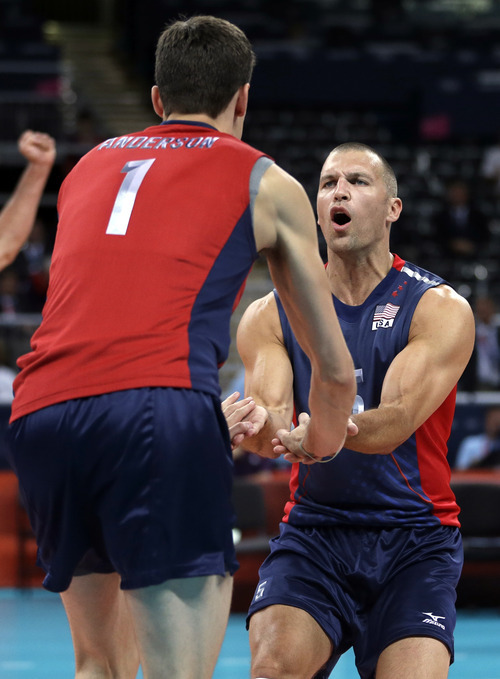United States' Matthew Anderson, left, and teammate Richard Lambourne celebrate after scoring a point against Serbia during a men's preliminary volleyball match at the 2012 Summer Olympics, Sunday, July 29, 2012, in London. (AP Photo/Jeff Roberson)