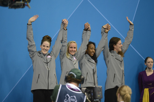 Missy Franklin, Jessica Hardy, Lia Neal and Allison Schmitt raise their arms n victory after being introduced as the Bronze Medalist in the Women's 4 x 100m Freestyle Relay during the evening session of the swimming competition Saturday, July 28, 2012 at the Aquatics Centre.  John Leyba, The Denver Post