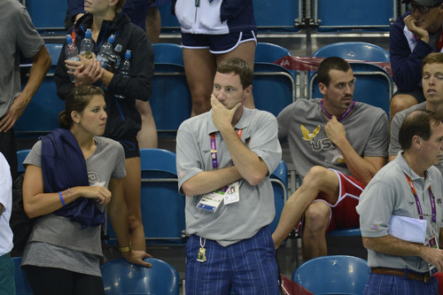 Missy Franlin's coach Todd Schmitz  watches the Medal ceremony after  the Women's 4 x 100m Freestyle Relay during the evening session of the swimming competition Saturday, July 28, 2012 at the Aquatics Centre.  John Leyba, The Denver Post