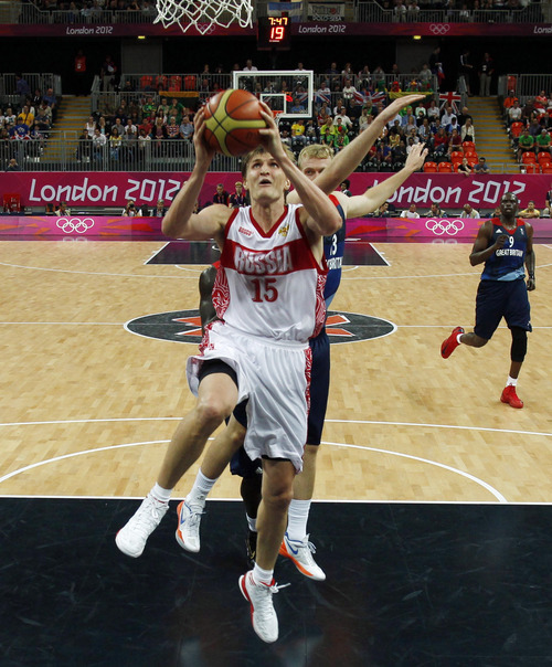 Russia's Andrei Kirilenko, center, goes to the basket during the men's group B basketball match against Britain, at the 2012 Summer Olympics on Sunday, July 29, 2012, in London. (AP Photo/Mike Segar, Pool)