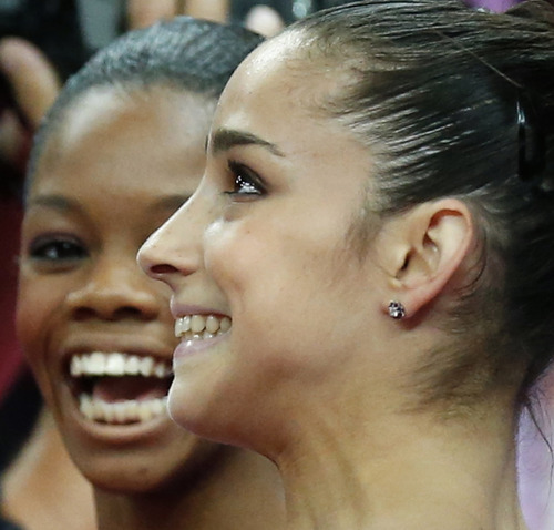 U.S. gymnasts Alexandra Raisman, right, and Gabrielle Douglas celebrate after qualifying for the women's all-around finals during the artistic gymnastics women's qualifications at the 2012 Summer Olympics, Sunday, July 29, 2012, in London. (AP Photo/Matt Dunham)