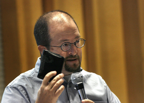 Scott Sommerdorf  |  The Salt Lake Tribune              Aaron Campbell holds up his wallet to emphasize his point about what makes most voters go to the polls during a presentation of Mormon voting patterns on July 28 at the Sunstone Symposium, held at the University of Utah.