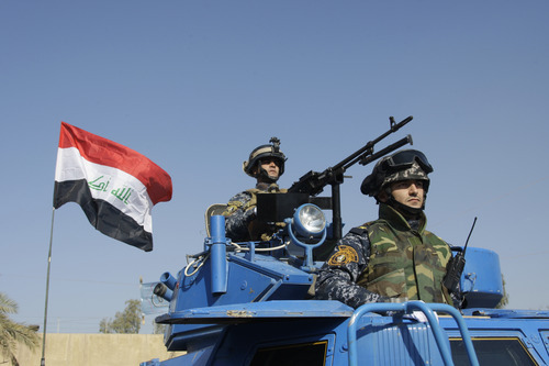 HOLD FOR RELEASE UNTIL 12:01 A.M., EDT, MONDAY, JULY 30, 2012 - PHOTO IS NOT TO BE PUBLISHED ONLINE OR BROADCAST UNTIL 12:01 A.M., EDT - FILE - In this Nov. 22, 2011 file photo, the Iraqi flag waves while federal police parade in Baghdad. A report by the U.S. Special Inspector General for Iraq Reconstruction, to be released Monday, July 30, 2012, found that the American Embassy in Baghdad never got a written commitment for Iraq to participate in what initially was envisioned as a five-year, multibillion-dollar effort to train security forces after the U.S. military left last December. (AP Photo/Khalid Mohammed, File)