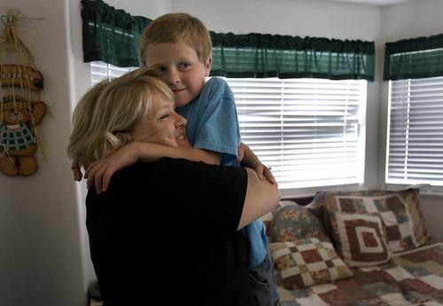 Scott Sommerdorf     The Salt Lake Tribune              Michelle Hilton hugs her autistic son, Logan, 6, after he said