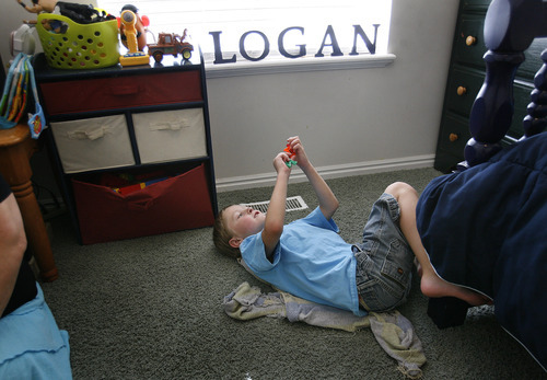 Scott Sommerdorf  |  The Salt Lake Tribune              Six-year-old Logan Hilton plays with magnetic letters in his room, Friday, July 27, 2012. His mother, Michelle Hilton, qualifies for a new pilot program to treat her autistic son. The problem is she needs to contribute $6,000 to fully benefit.