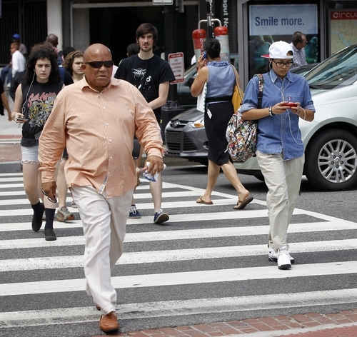 In this photo taken July 10, 2012, Pedestrians cross K Street and Connecticut Ave. NW near the Farragut North Metro Entrance in downtown Washington. Across the country on city streets, in suburban parking lots and in shopping centers, there is usually someone strolling while talking on a phone, texting with their head down, listening to music, or playing a video game. The problem isn't as widely discussed as distracted driving, but the danger is real. (AP Photo/Pablo Martinez Monsivais)