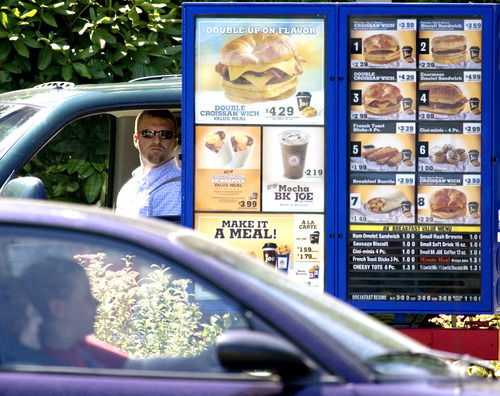 FILE - In this July 31, 2008 file photo, customers view the menu in the drive through line at a Burger King in Portland, Ore.  When the Obama administration agreed to set the first-ever federal limits on runoff in Florida, environmental groups thought the state's waters would finally get clean from a nutrient overdose that spawns algal blooms, suffocates rivers, lakes and streams, and forms byproducts in drinking water that could make people sick. The Florida rule is one of a string of regulations delayed at federal agencies, or at the White House office responsible for reviewing new rules. Together, they highlight the administration's cautiousness in an election year, where it has been increasingly under attack by Republicans and business groups for favoring big government and costly regulations that they allege kill jobs..  (AP Photo/Don Ryan, File)
