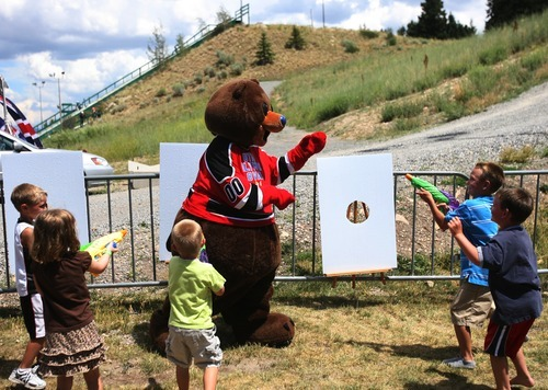 Kim Raff  |  The Salt Lake Tribune Utah Olympic mascot Coal is surrounded by a group of children shooting him with water guns during a London Summer Olympics celebration at Utah Olympic Park in Park City, Utah on July 28, 2012.