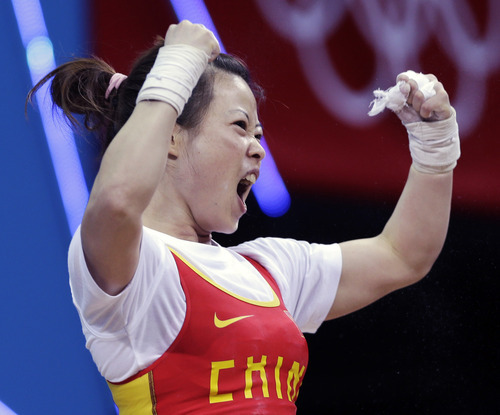China's Wang Mingjuan reacts during the women's 48-kg weightlifting event where she won the gold medal at the 2012 Summer Olympics, Saturday, July 28, 2012, in London. (AP Photo/Mike Groll)