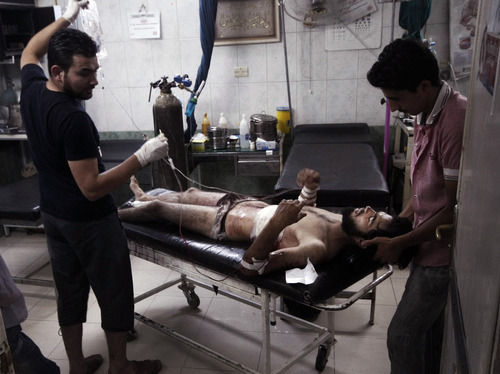 In this Sunday, July 29, 2012 photo, medics help a wounded man at the border town of Azaz, some 20 miles (32 kilometers) north of Aleppo, Syria. The U.N. said 200,000 Syrians have fled the embattled city of Aleppo since intense clashes between regime forces and rebels began 10 days ago. The government forces turned mortars, tank and helicopter gunships against rebel positions on Monday, July 30, 2012. (AP Photo/Turkpix)
