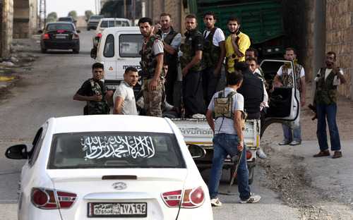 In this Sunday, July 29, 2012 photo, Free Syrian Army soldiers are seen at the border town of Azaz, some 20 miles (32 kilometers) north of Aleppo, Syria. The U.N. said 200,000 Syrians have fled the embattled city of Aleppo since intense clashes between regime forces and rebels began 10 days ago. The government forces turned mortars, tank and helicopter gunships against rebel positions on Monday, July 30, 2012. (AP Photo/Turkpix)