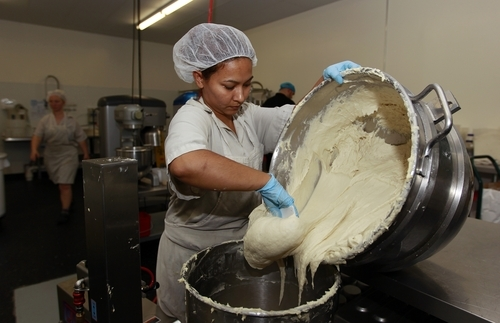 In this Thursday, July 14, 2012 photo, Bertha Domimguez prepares gluten-free dough at Pure Knead bakery sandwich bread in Decatur, Ga. Scientists suggest that there may be more celiac disease today because people eat more processed wheat products than in decades past, which use types of wheat that have a higher gluten content. Or it could be due to changes made to wheat, said the Mayo Clinic's Dr. Joseph Murray. In the 1950s, scientists began cross-breeding wheat to make hardier, shorter and better-growing plants. It was the basis of a so-called
