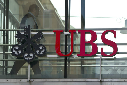 FILE - In thos June 22, 2012 file photo a man walks past the logo of the UBS bank in Zurich, Switzerland. UBS AG posted second-quarter net profits of 425 million Swiss francs (US$434.16 million) Tuesday, July 31, 2012, a sharp plunge from the 1.02 billion Swiss francs (US$1.2 billion) it posted in the comparable period a year ago. Hit by lower trading revenue and fewer commissions and client fees, Switzerland's largest bank said the 58 percent net profit drop reflects