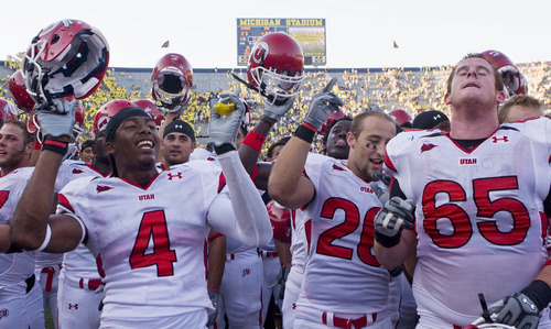 Utah defensive back Sean Smith, left, linebacker Mike Wright, middle, and offensive lineman Dustin Hensel, right, celebrate with teammates after beating Michigan 25-23 on Saturday, Aug. 30, 2008, in Ann Arbor, Mich. (AP Photo/Tony Ding)