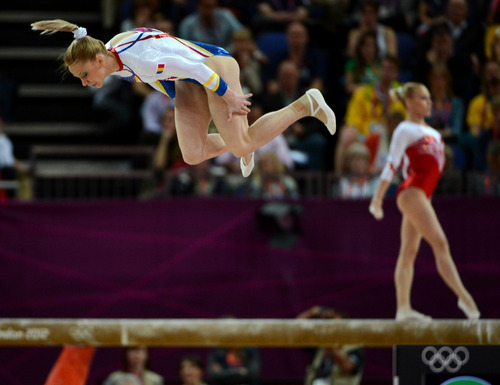 Romania's Sandra Raluca Izbasa, left, competes on the floor while Russia's Kseniia Afanaseva competes on the balance beam during the Women's Gymnastics Team finals at North Greenwich Arena for the London 2012 Olympics in London, England on Tuesday, July 31, 2012.  (Nhat V. Meyer/Mercury News)