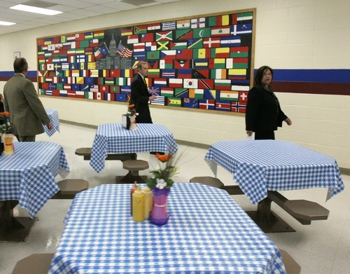 U.S. Immigration and Customs Enforcement officials, Marc Moore, left, and Gary Mead, center, along with Corrections Corporation of America Administrator, Evelyn Hernandez, right, talk in April 22, 2008, about a mural of flags as well as the table cloths and flowers added to the cafeteria at the T. Don Hutto Residential Center in Taylor, Texas, during a tour for the media.  The U.S. is locking up more illegal immigrants than ever before, generating a lucrative business for the nation's largest prison companies. (AP Photo/Donna McWilliam, Pool, File)