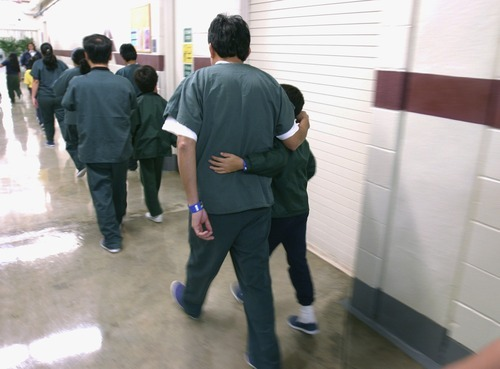 Family detainees walking down the hall at the T. Don Hutto Residential Center in Taylor, Texas, in February 2007. The U.S. is locking up more illegal immigrants than ever before, generating a lucrative business for the nation's largest prison companies. (AP Photo/Department of Homeland Security, Charles Reed, HO, File)